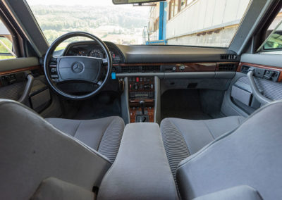 Mercedes-Benz 560 SEL - L'espace avant est séparé par une console centrale imposante.