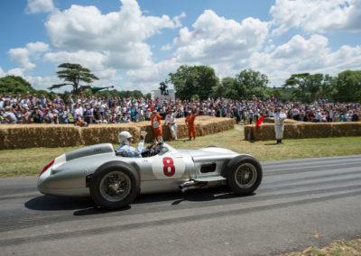 Sir Stirling Moss au volant de la Mercedes-Benz Silver Arrow W 196 R en 2015 au Goodwood Festival saluant le public et les commissaires.